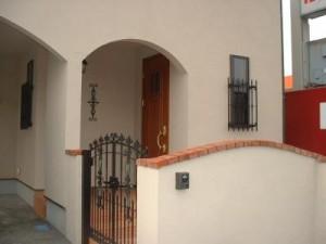 エントランスも南欧風に近づけるようにアールを使い工夫しました。塀も外壁と同じ材料を使い、統一感を出しました。門扉、面格子は鋳鉄製のものを使っています